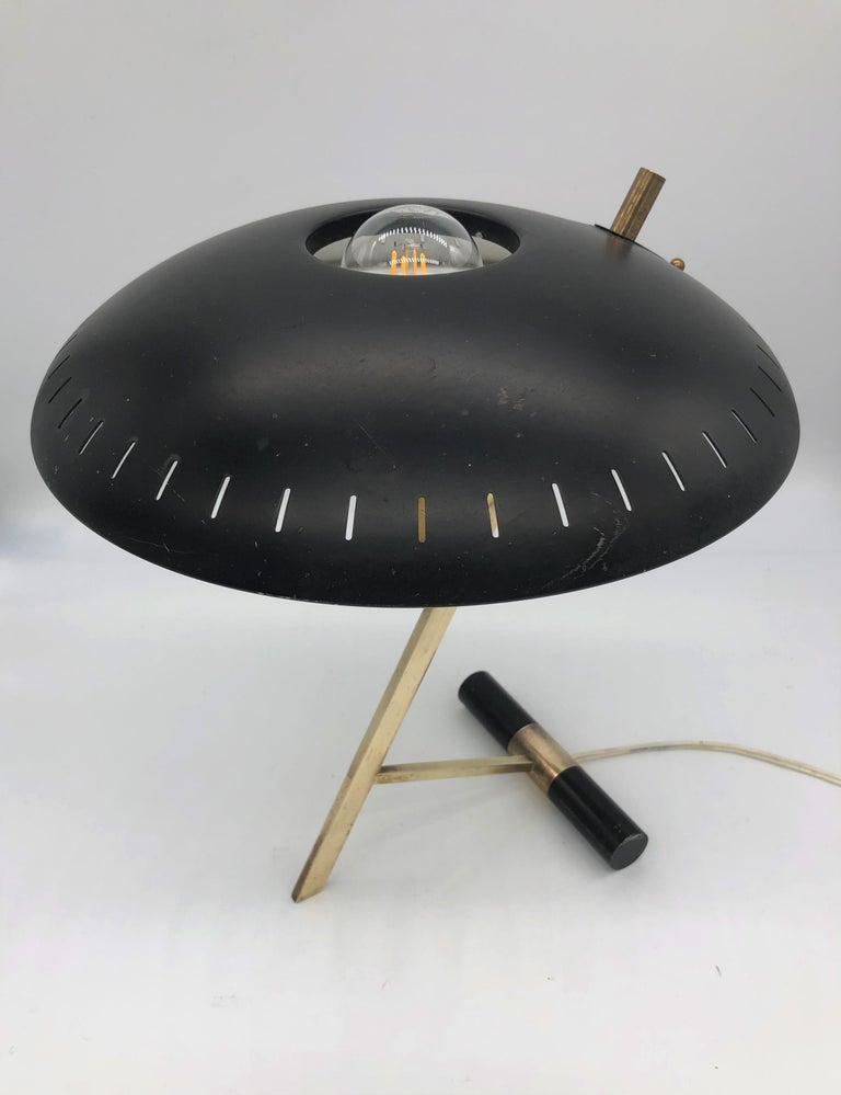 This table lamp designed by Louis Kalff in the 1950s and manufactured by Phillips is an iconic piece of 20th century design. The domed black lacquered metal shade stands on top of a gilt-brass foot. This model, named Z after its shape, is stamped