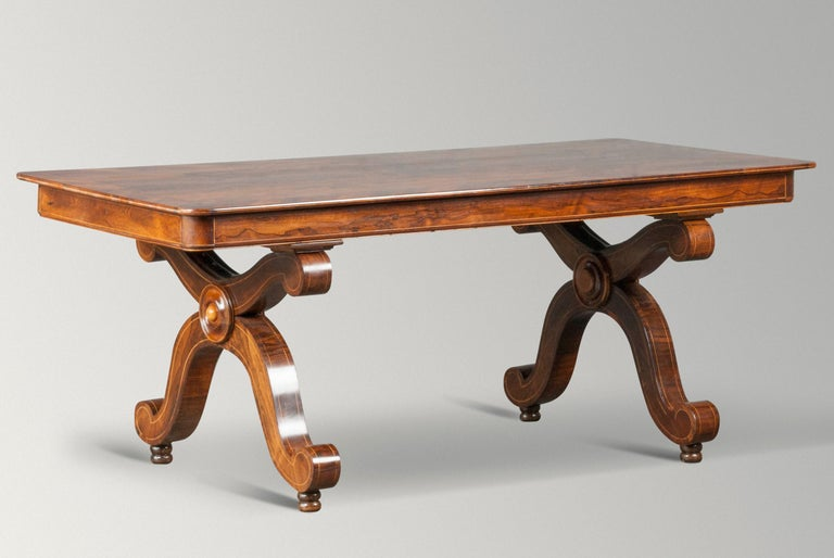 Nice antique French table or desk. Mahogany veneered, the tabletop has rounded corners and a fine edge of light wood. The table has a beautiful patina, nice warm color. The X legs are designed with decorative curls. The table is dismountable, both