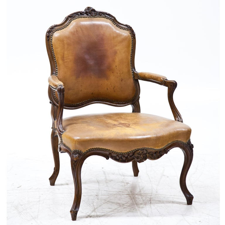 Armchair standing on S-legs with curved frame and carved floral decorations. The trapezoidal seat as well as the back and armrests are covered with riveted leather. The slightly set back armrests rest on curved, rocaille-shaped supports. The curved