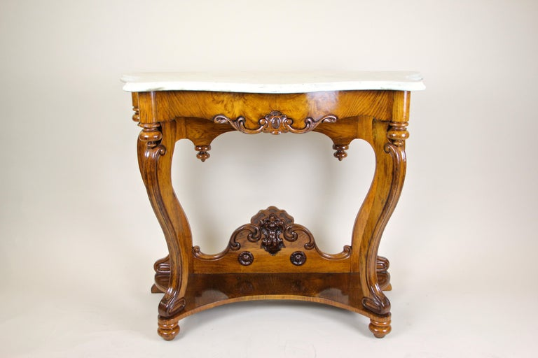 Exceptional hand carved Louis Philippe console with Carrara marble plate out of France, circa 1850. Processed of fine oakwood - partly solid/ partly veneered - this unique French masterpiece impresses with its absolute gorgeous design adorned by