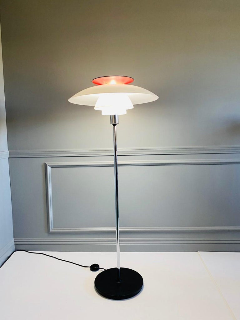 Incredible piece of design. The fixture diffuses light beautifully. The opal acrylic shades emit a comfortable room lighting while the red hue of the top reflector helps give the light a warmer glow. Classic piece of lighting design.