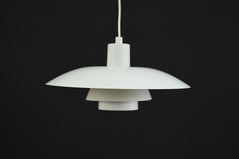 This pendant light was designed was Poul Henningsen for Louis Poulsen as part of Henningsen's groundbreaking three shade system that uses metal shades to direct uniform, downwards lighting. This model PH4/3 pendant light has a clean, modern look