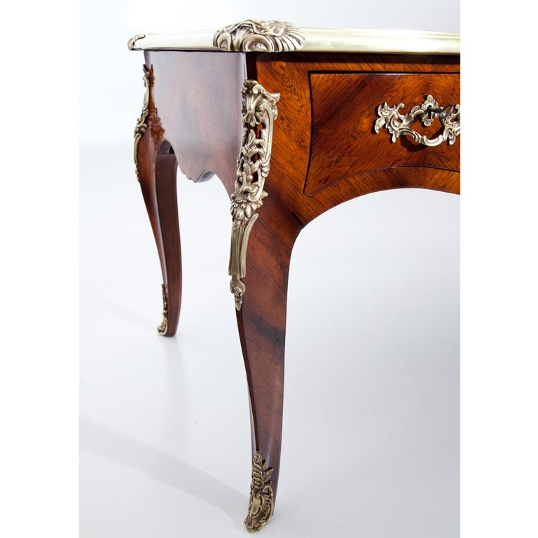 Large Louis-Quinze-style desk in mahogany veneered. The writing surface is covered in brown leather, the edges are decorated with brass profiles. The desk has three drawers, which are imitated on the back. The curved legs show decorative fittings in