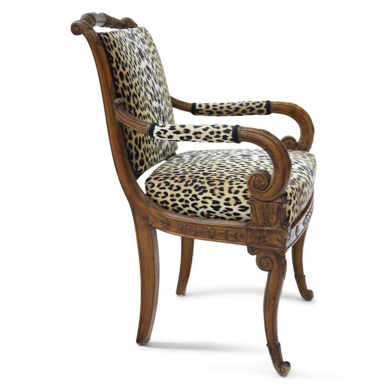 Armchair with neoclassical carvings on the railing, the armrests and backrest. The chair stands on volute-shaped feet in the front and slightly curved legs in the back. The armrests end in volutes. Seat and backrest are upholstered with a leopard