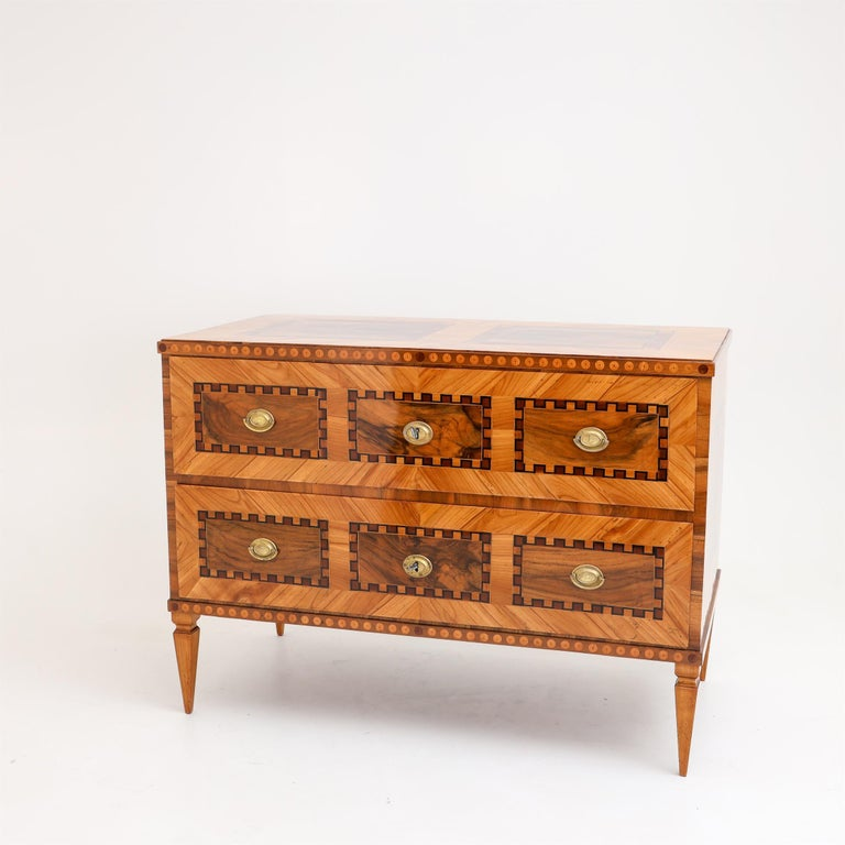 Louis Seize chest of drawers on square tapering feet with two drawers. Framing marquetry work on all sides. The chest of drawers has been professionally restored and hand polished.