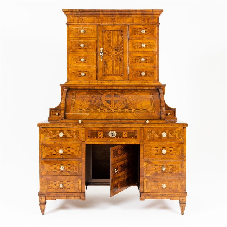 Louis Seize secretaire with square pointed feet and three-quarter cylinder door as well as a high top with straight profiled cornice, a tabernacle compartment and eight further drawers. The roll top door is flanked on the sides by concave elements
