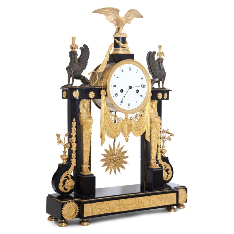 Louis Seize portal clock with eagle and sphinx decoration as well as Egyptian herms and frieze with putti on the base. Black marble and fire-gilded bronze. The work signed Dufue à Lyon.
