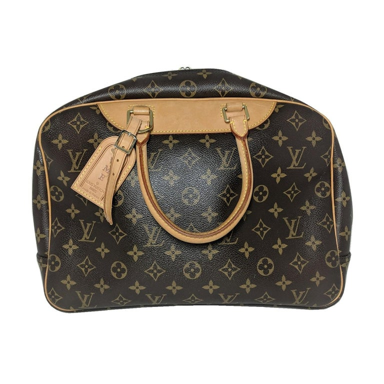 This Louis Vuitton Monogram Deaville Canvas Bowling bag, is crafted from brown and tan monogram coated canvas, features dual rolled top handles, cowhide leather trim, and brass hardware. Its two-way zip-around closure opens to a beige canvas lining