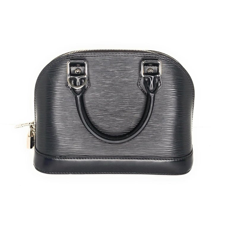 Black EPI leather Louis Vuitton Alma BB with silver-tone hardware, single detachable flat shoulder strap, dual rolled top handles, protective feet at base, gray microfiber interior, single interior slit pocket and two-way zip closures at top. Retail