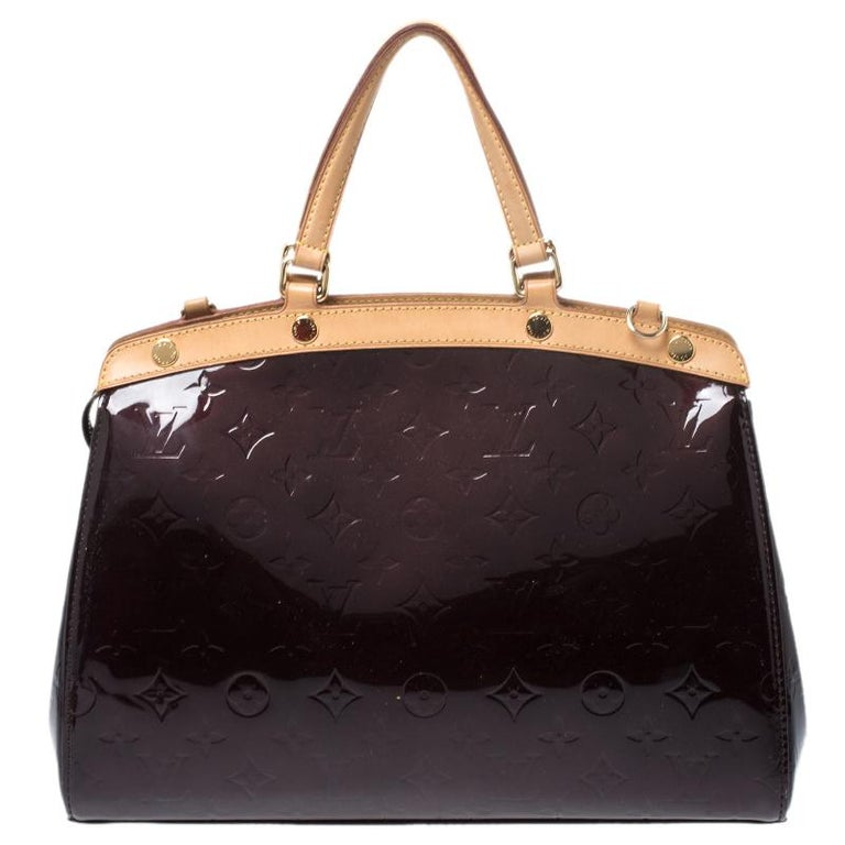 The feminine shape of Louis Vuitton's Brea is inspired by the doctor's bag. Crafted from Monogram Vernis in burgundy, the bag has a perfect finish. The fabric interior is spacious and it is secured by a zipper. The bag features double handles,