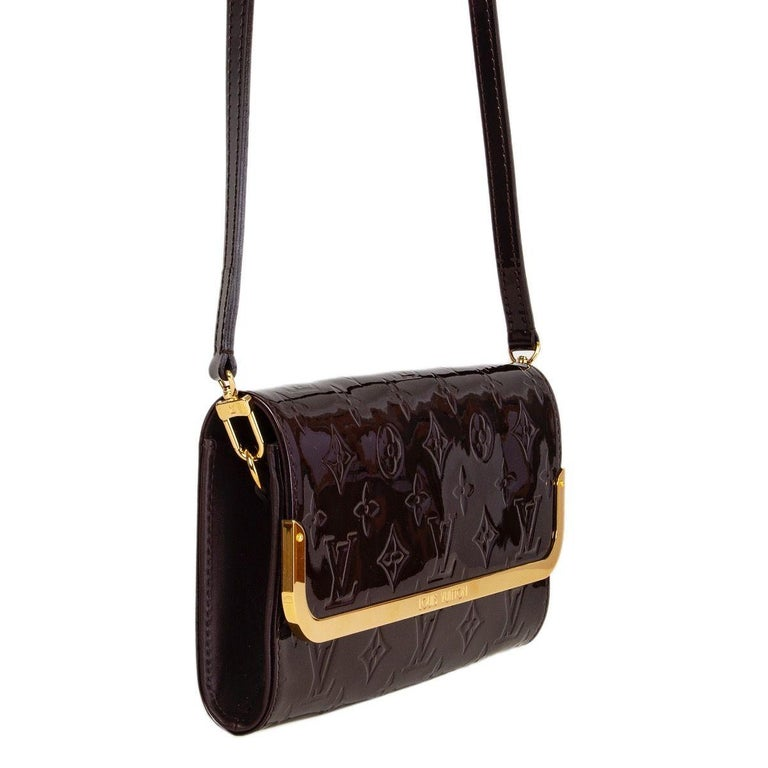 Louis Vuitton 'Rossmore MM' bag in Amarante (eggplant) Monogram Vernis leather. Detachable shoulder strap. Two open pockets on the outside back. Closes with a magnetic-snap under the flap. Lined in fabric with a zipper pocket against the front and