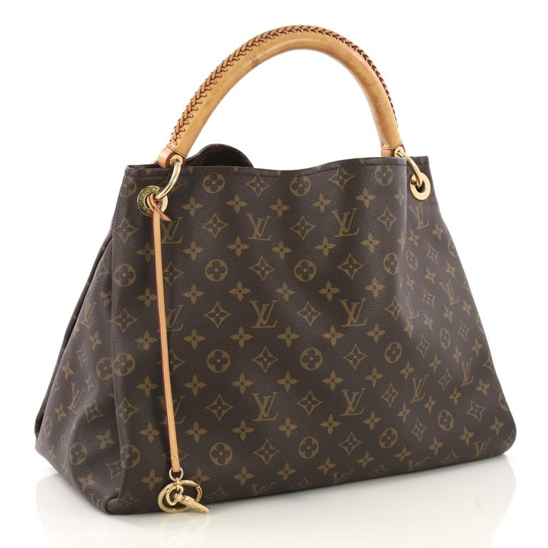 This Louis Vuitton Artsy Handbag Monogram Canvas MM, crafted from brown monogram coated canvas, features a rolled leather handle with braided detailing, protective base studs, and gold-tone hardware. It opens to a beige microfiber interior with side