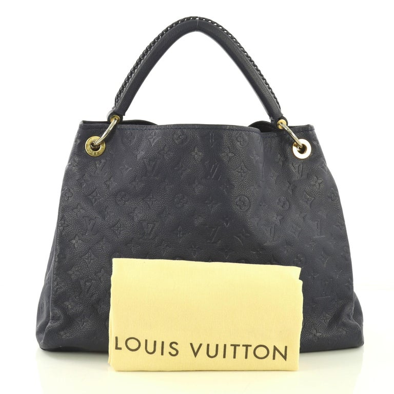 This Louis Vuitton Artsy Handbag Monogram Empreinte Leather MM, crafted from navy blue monogram empreinte leather, features a single looped braided top handle, protective base studs, and gold-tone hardware. Its wide open top showcases a navy blue