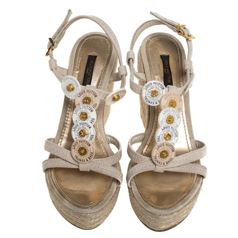 Walk with comfort in these lovely sandals from Louis Vuitton! The sandals have been crafted from canvas and styled with medallion details on the vamps. They flaunt ankle closure and espadrille platform wedge heels.  Includes: Original Box