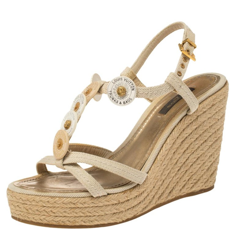 Walk with comfort in these lovely sandals from Louis Vuitton! The sandals have been crafted from canvas in an open toe silhouette and styled with medallion details on the vamp straps. They flaunt ankle straps with buckle fastenings and 11 cm