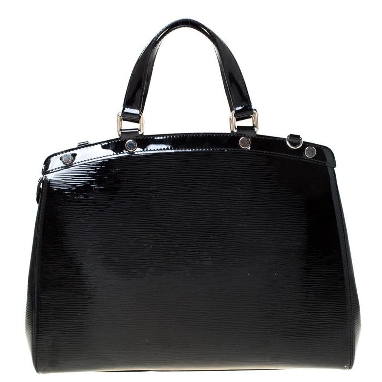 The feminine shape of Louis Vuitton's Brea is inspired by the doctor's bag. Crafted from Epi leather in black, the bag has a perfect finish. The fabric interior is spacious and it is secured by a zipper. The bag features double handles, protective
