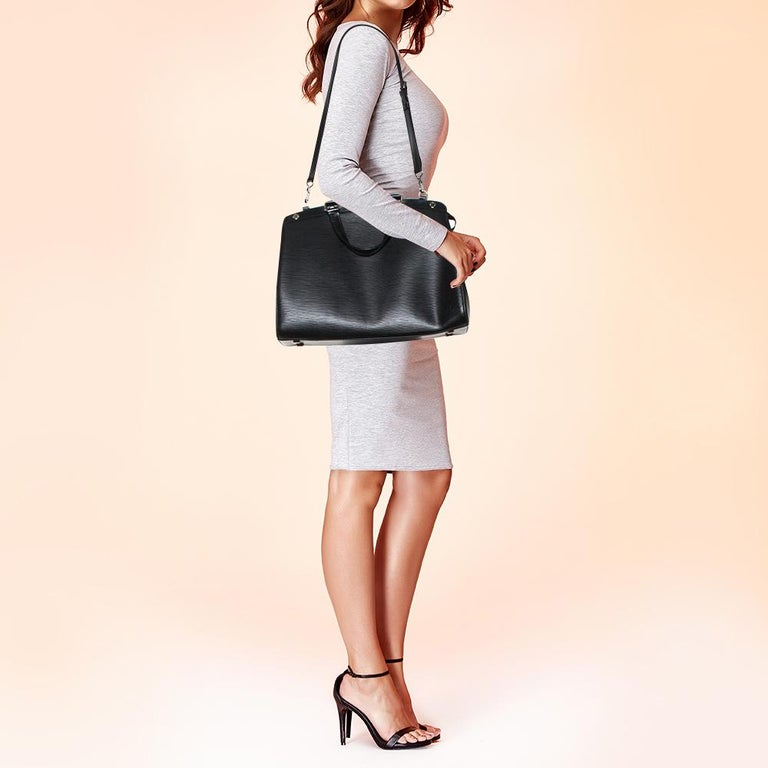 The sophisticated shape of Louis Vuitton's Brea makes it a highly coveted piece. Crafted from Epi Leather in black, the bag has a perfect finish. The fabric interior is spacious and it is secured by a zipper. The bag features double handles,