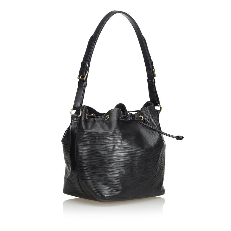 The Petit Noe features Epi leather, an adjustable shoulder strap, a drawstring closure, Alcantara lining, and an interior zip pocket. It carries as B condition rating.  Inclusions:  This item does not come with inclusions.   Louis Vuitton pieces do