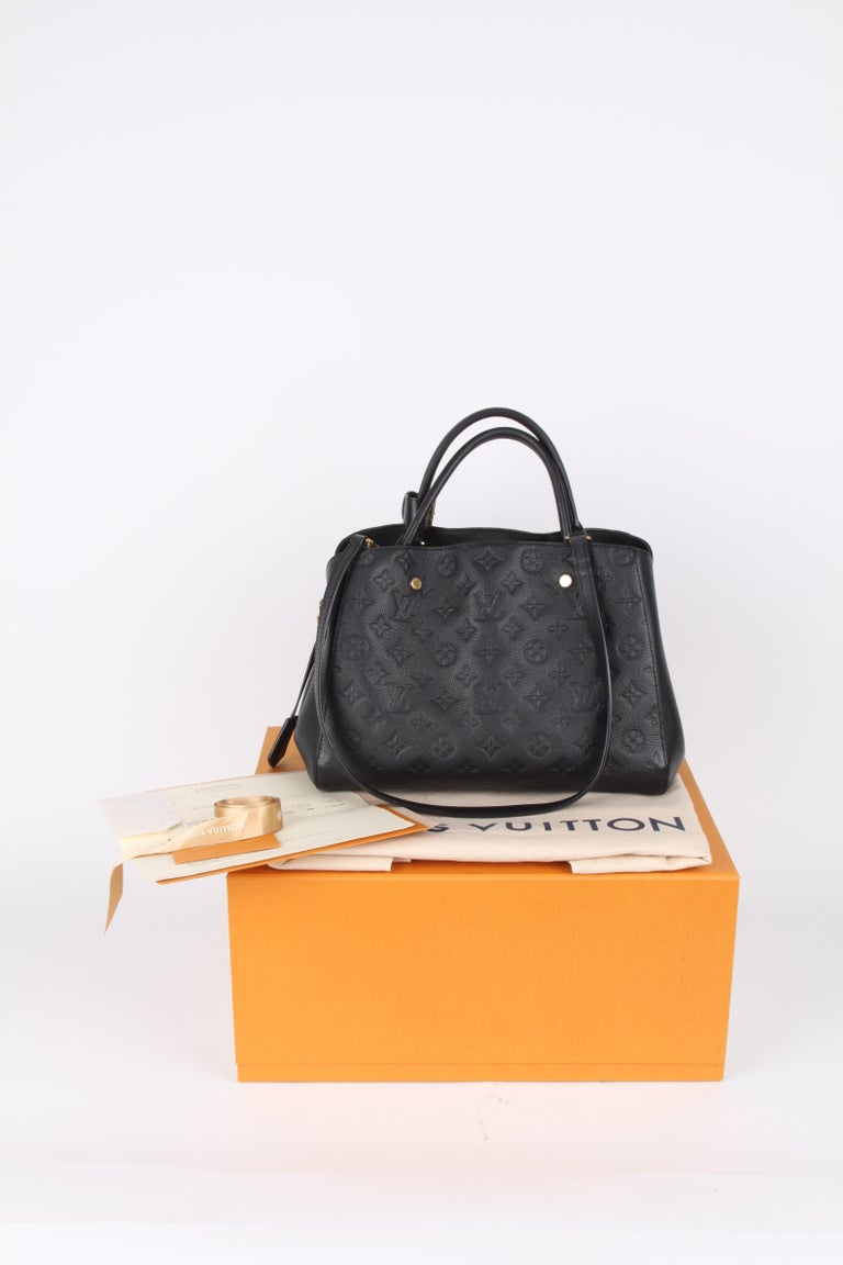 Louis Vuitton Black Monogram Empreinte Montaigne MM Handbag.  Named after the most elegant avenue in Paris, the Montaigne MM handbag is both chic and impeccably functional. Made from Monogram Empreinte leather, this model is an ideal business bag:
