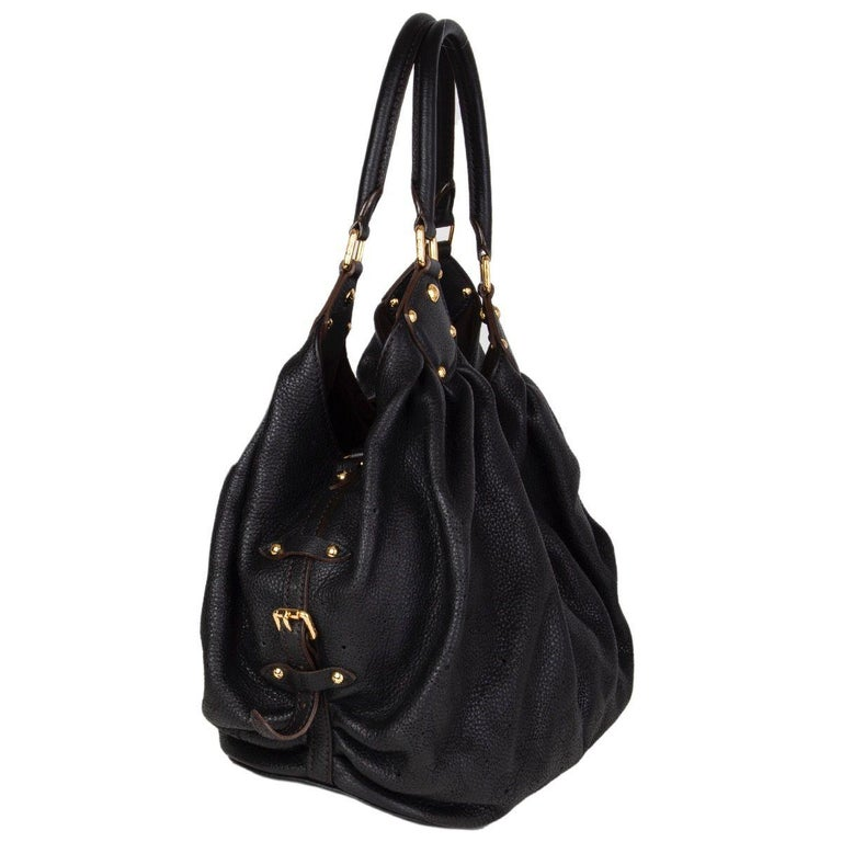 Louis Vuitton 'Mahina MM' hobo bag in black perforated monogram leather and it features two handles and gold-tone hardware. The push-lock opens to a spacious dark brown alcantara lined interior with one zipper pocket against the back and a D ring.