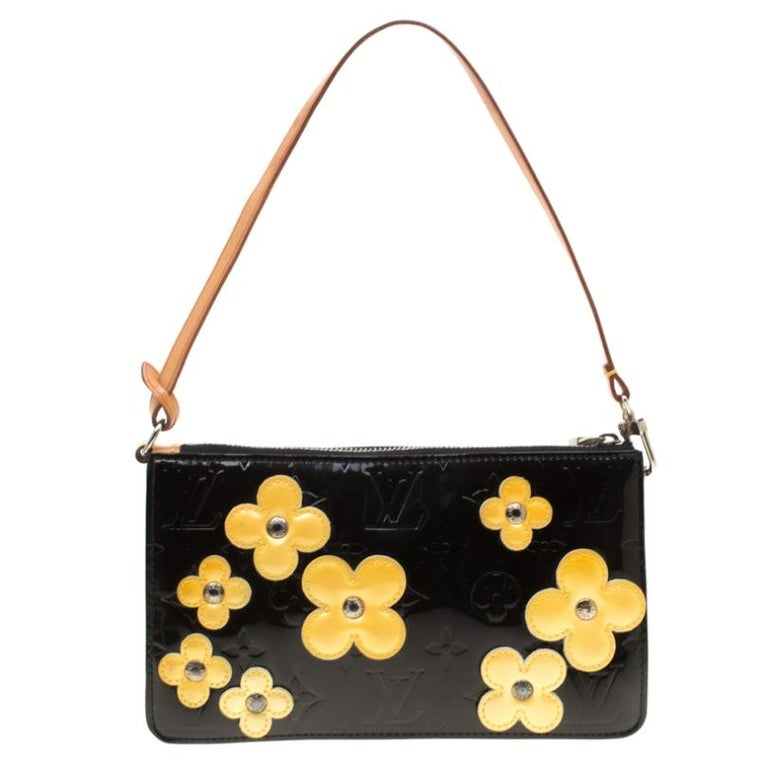 This Louis Vuitton pochette is limited edition which means that you will be amongst only a handful of women to own one of these. It comes crafted from monogram Vernis and decorated with floral appliques. It features a zipped leather interior and a