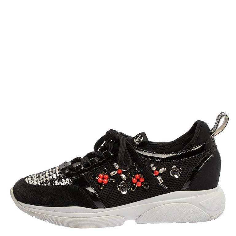 Louis Vuitton glams up the classic sneakers with this pair. Crafted from black patent leather & suede, they feature mesh panels on the quarters embellished with jewel accents while the vamps are adorned with sequined embroidery. These sneakers come