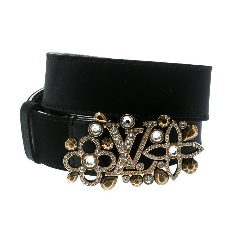 This gorgeous Runway belt from Louis Vuitton will lend an extra character to your chic, statement dresses. This belt, crafted from satin and leather trims, features a beautiful rhinestones-encrusted gold LV monogram buckle. The buckle is surrounded