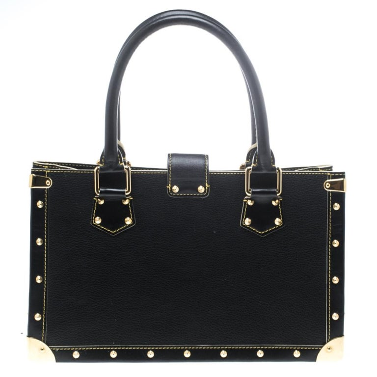 Louis Vuitton's Le Fabuleux bag looks nothing like a regular Louis Vuitton bag! Rectangular in shape the bag is crafted from black suhali leather and has stud embellishments. It features dual top handles, a front zip pocket, and a S lock closure.