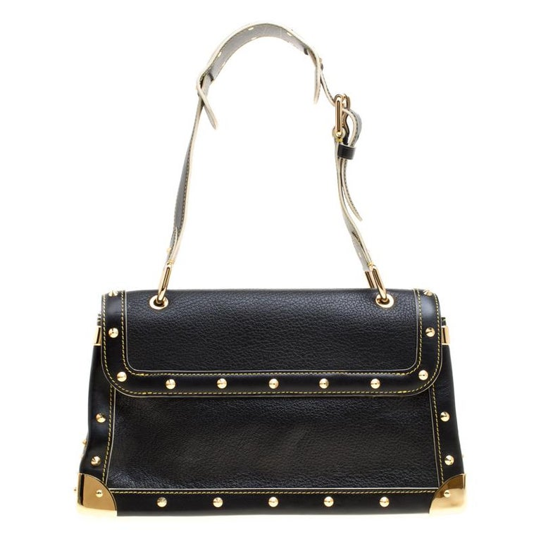 This Suhali Le Talentueux bag from Louis Vuitton is gorgeous. The black beauty is crafted from leather and flaunts a unique and distinctive style. It features beautiful gold-tone pyramid studs, a push lock closure, rings and metal reinforced edges,