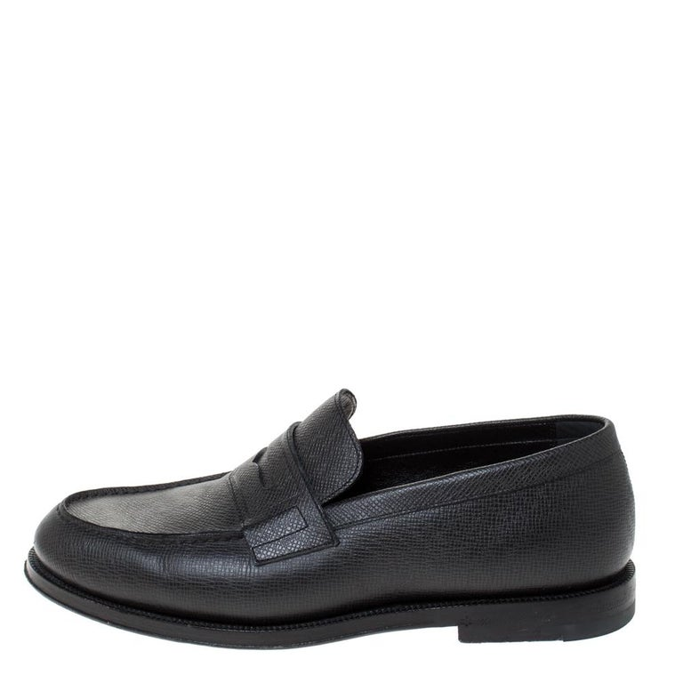 These black loafers made from textured leather reflect comfortable fashion and classic style. Designed to excellence, this pair is from the leading luxury house of Louis Vuitton, and it arrives with tough soles and penny keeper straps.  Includes: