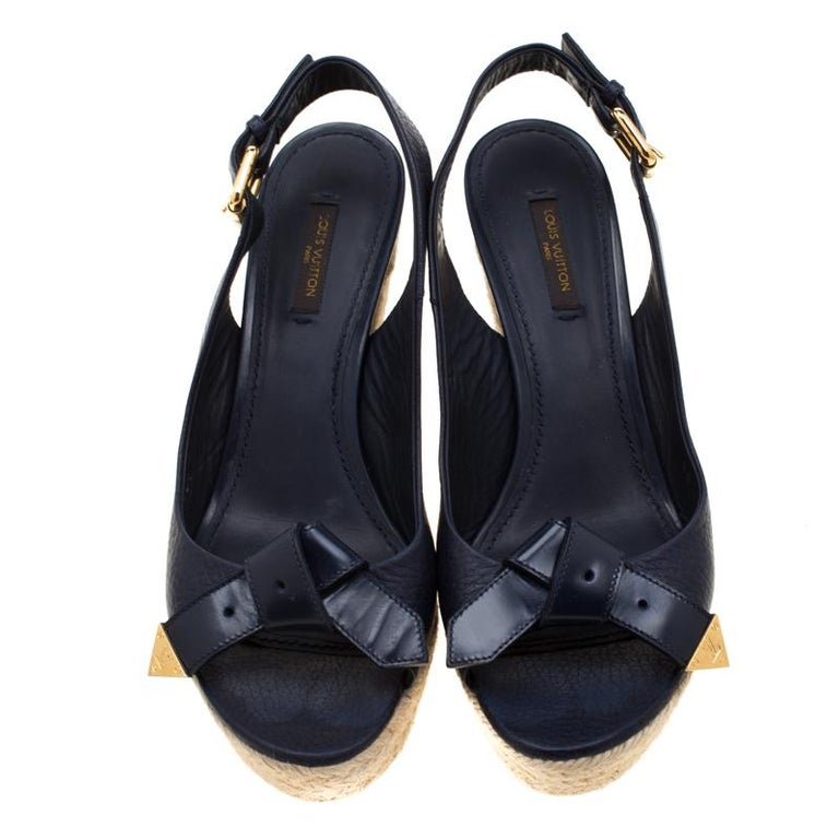 Wear them through the day or dress them up for day time parties, these Louis Vuitton open toe sandals are stylish and comfortable. With a blue leather surface that features knot details at the front, these shoes feature espadrille wedges that give