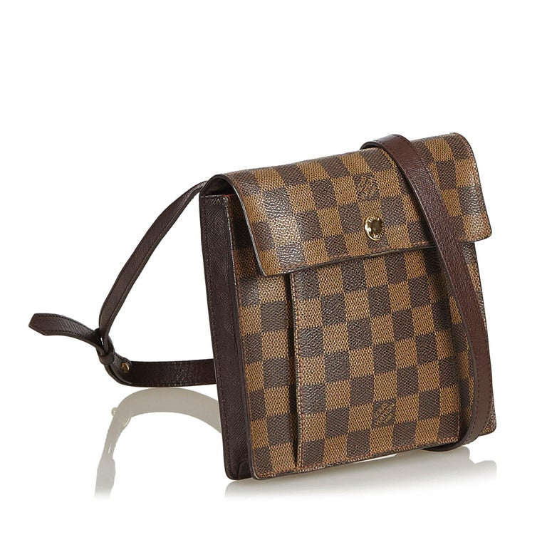 The Pimlico features a damier ebene canvas body, flat adjustable leather strap, and front flap with button snap closure. It carries as B condition rating.  Inclusions:  This item does not come with inclusions.   Louis Vuitton pieces do not come with