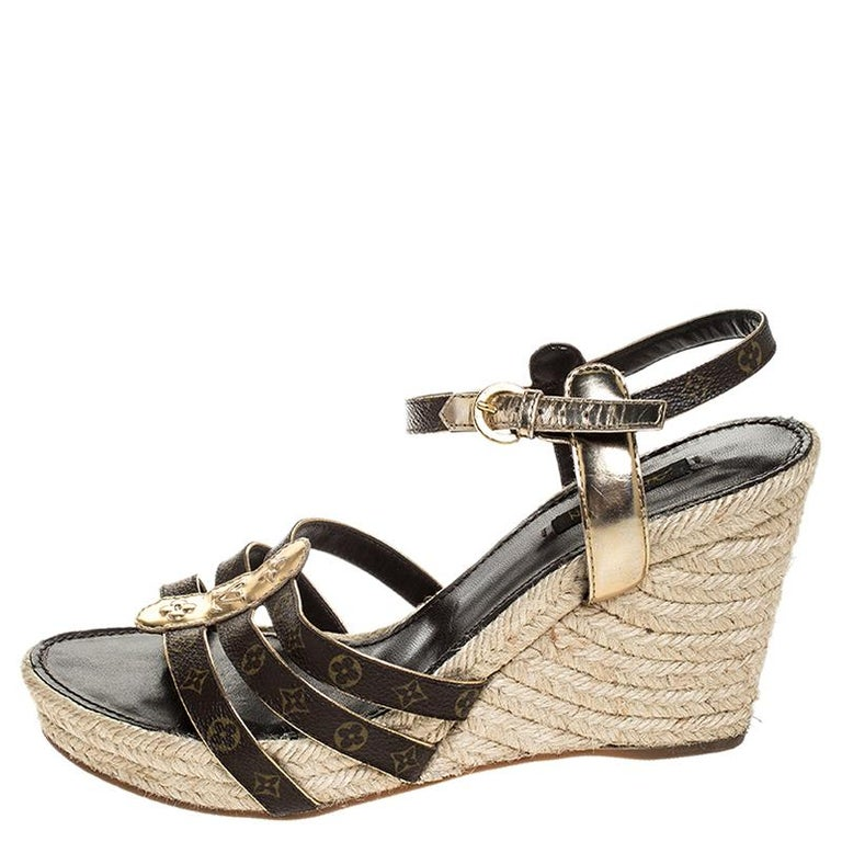 A perfect blend of comfort and style, these leather and Monogram coated canvas sandals come from the iconic house of Louis Vuitton. This espadrille pair is designed in an elegant shade of brown, features gold leather trims, 10.5 cm wedge heels and a