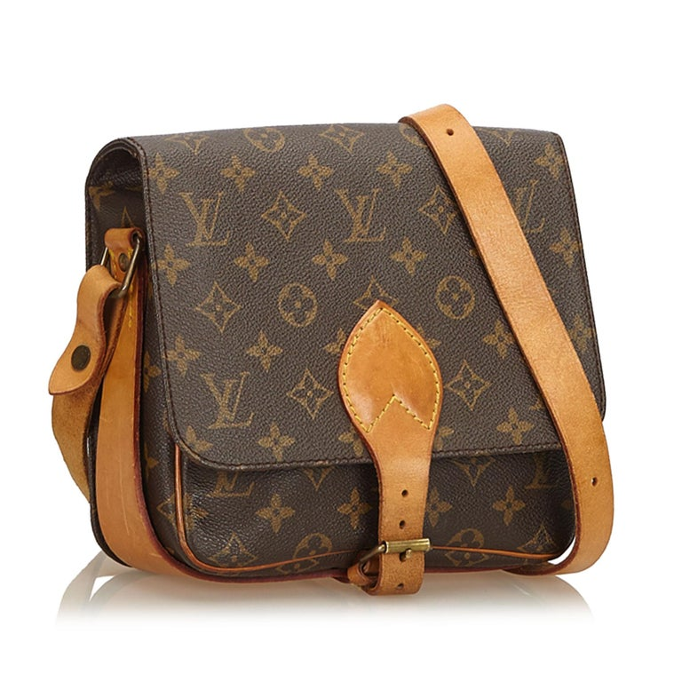 The Cartouchiere MM features a monogram canvas body, an adjustable leather strap, a front flap with a belt buckle closure, and an interior open compartment. It carries as B condition rating.  Inclusions:  Dust Bag   Louis Vuitton pieces do not come
