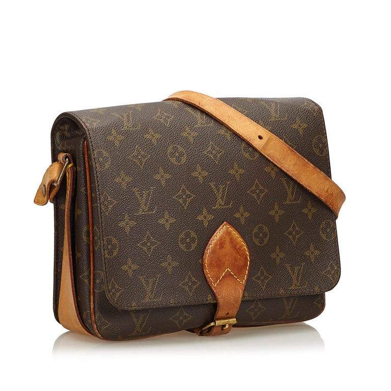 The Cartouchiere GM features a monogram canvas body, an adjustable leather strap, a front flap with a belt buckle closure, and an interior open compartment. It carries as B condition rating.  Inclusions:  This item does not come with