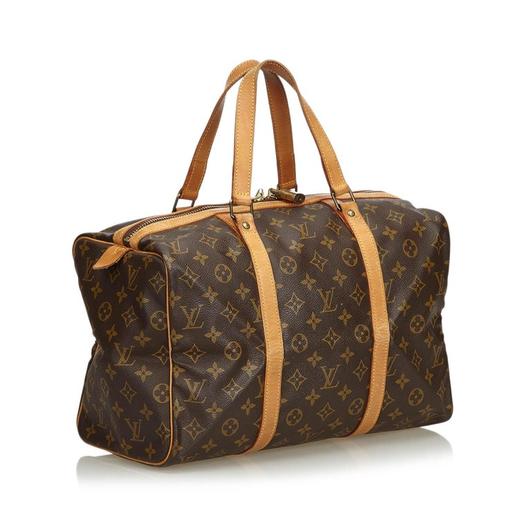 The Sac Souple 35 features a monogram canvas body, flat leather straps, and a top zip closure. It carries as B condition rating.  Inclusions:  Padlock   Louis Vuitton pieces do not come with an authenticity card�please refer to the production date