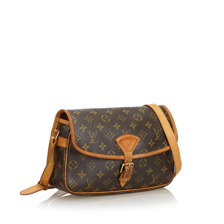 The Sologne features the monogram canvas, an adjustable flat vachetta strap with a vachetta shoulder pad, vachetta trim, a front flap secured by a belt and buckle closure, exterior front and back pockets, and an interior pocket. It carries as B