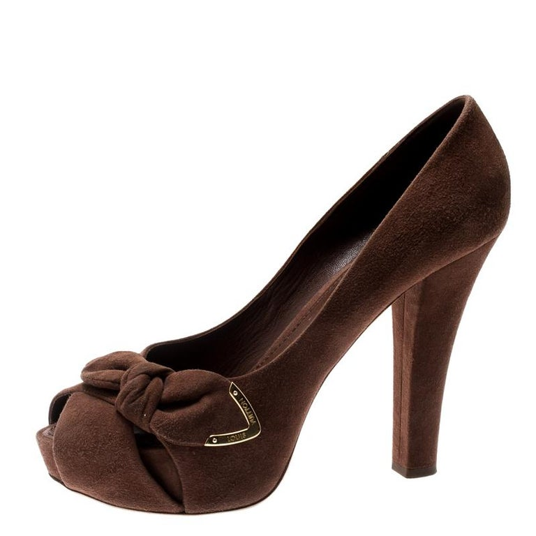 From Louis Vuitton's Spring 2011 collection, these 'Catania' peep toe pumps are crafted in brown suede and are adorned with ruched bow detailing and gold-tone LV-engraved plaques. These beauties sit on 11.5cm heels to lend you an elegant