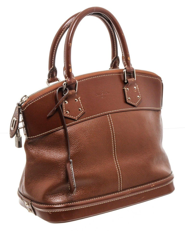 Cognac Suhali leather Louis Vuitton Lockit PM with silver-tone hardware, tonal smooth leather trim, dual rolled top handles, contrast stitching throughout, tonal monogrammed woven lining, single interior zip pocket at wall and zip closure at