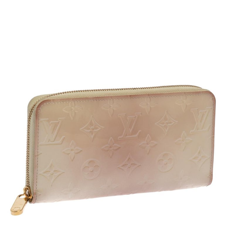 Designed in a cream white hue color, this wallet is a shimmering beauty. Its Monogram Vernis exterior is embossed with the LV signature motifs and features an all-around zip closure. Lined with leather, its interior includes multiple compartments