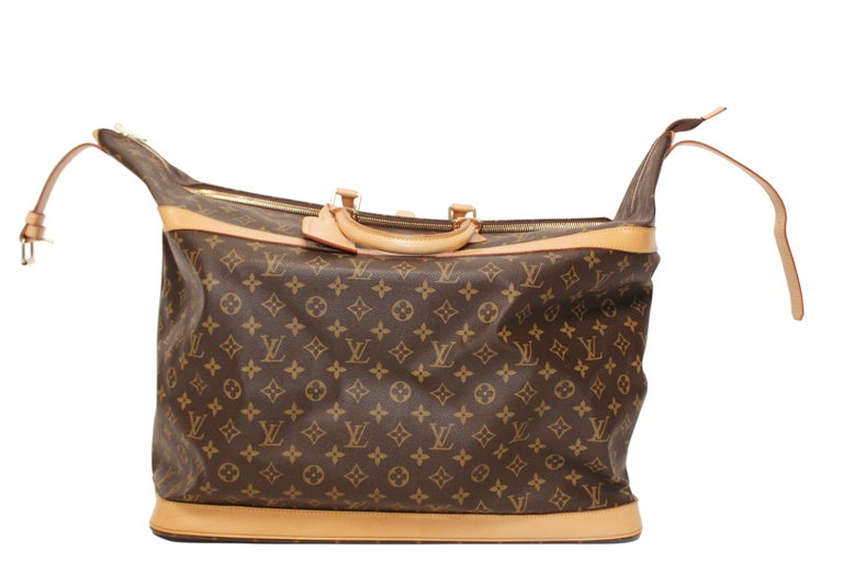 Louis Vuitton monogram vachetta leather and coated canvas Cruiser 50 travel bag with fabric interior. This spacious, light weight, hand held bag features leather top handles, top buckle with silver toned hardware and light tan leather trim