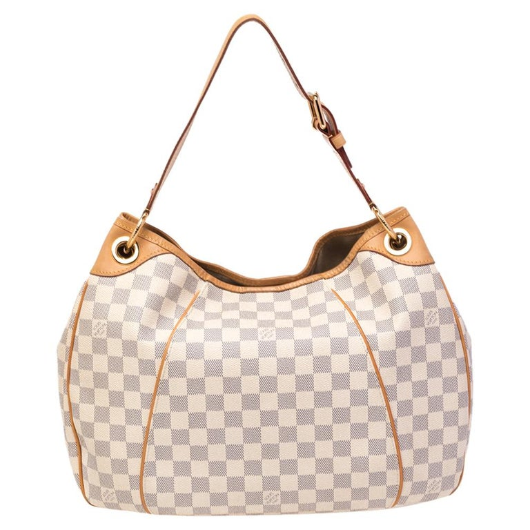 Add this Galliera bag by Louis Vuitton to your collection today! It is crafted with the signature Damier Azur canvas and leather on the exterior. It comes with a single handle, a snap button, and gold-tone hardware. The Louis Vuitton Inventeur plate