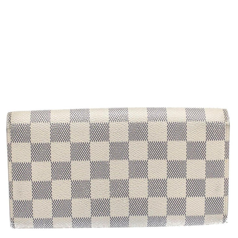 One of the most famous wallets by Louis Vuitton is the Sarah. This one here comes made from Damier Azur canvas and the button on the flap opens to an interior with multiple card slots and a zip pocket. Perfect in size, this wallet can easily fit