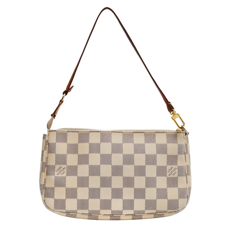 This pochette is crafted with of Louis Vuitton's signature Damier canvas in blue and white. The bag features a vachetta strap and a brass top zipper that opens to a beige fabric interior with a patch pocket.  COLOR: Damier Azur MATERIAL: Coated