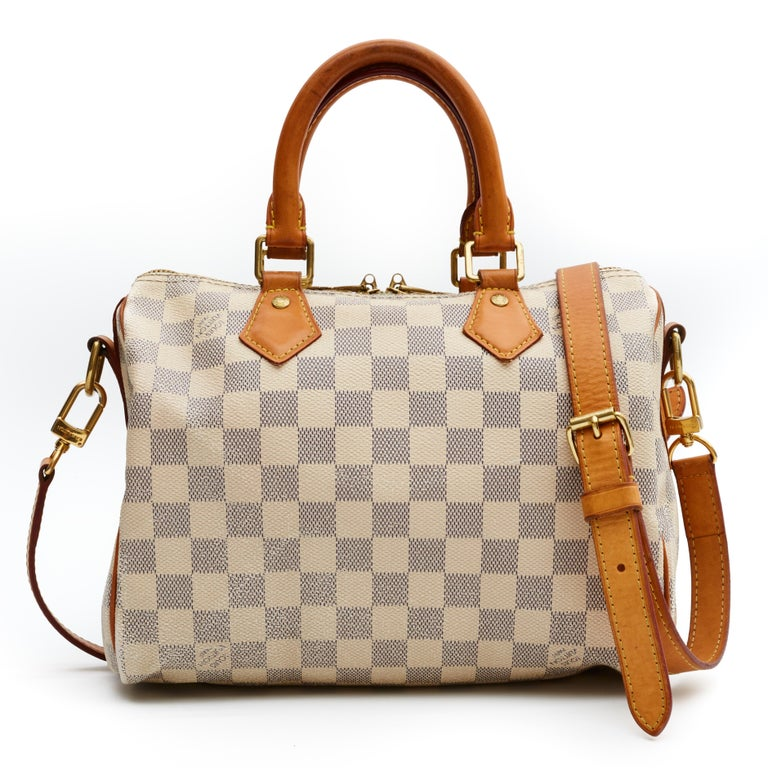 This style Speedy 25 Bandouliere (French for shoulder strap) is made with white canvas with Damier Azur print and features gold tone hardware, natural leather finishes, rolled leather handles, top zip closure and comes with an adjustable shoulder