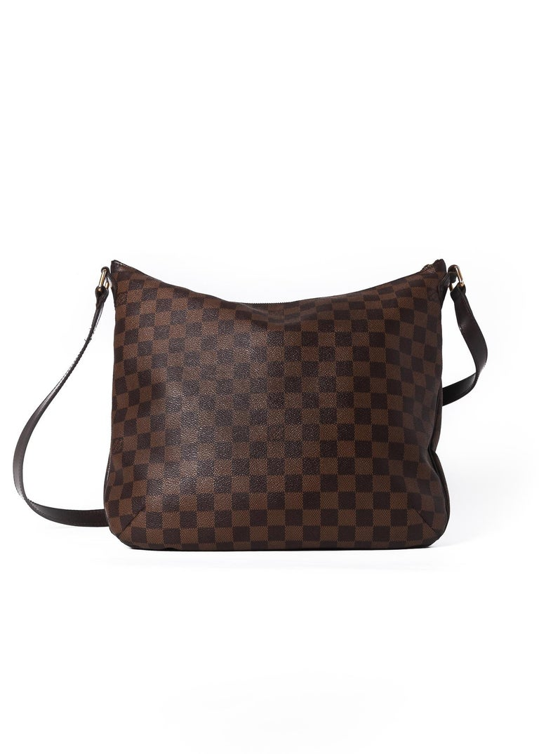 This Bloomsbury PM bag is made with Damier Ebene canvas and features brass hardware, exterior pocket, red woven fabric interior lining, top zip closure and an adjustable long shoulder strap. (Damier is French for checkerboard)  COLOR: Brown/Damier