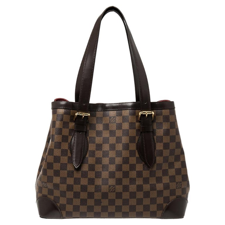 Handbags from Louis Vuitton enjoy widespread popularity owing to their high style and functionality. This Hampstead bag is no exception. Crafted from their signature Damier Ebene canvas and leather, the bag comes with two flat top handles and a hook