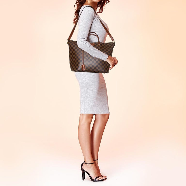 Louis Vuitton's Belmont bag is designed to assist you seamlessly in putting your best foot forward. Carrying it will always be a delight! It comes crafted from the signature Damier Ebene canvas and features dual top handles. It has dual zippers, a