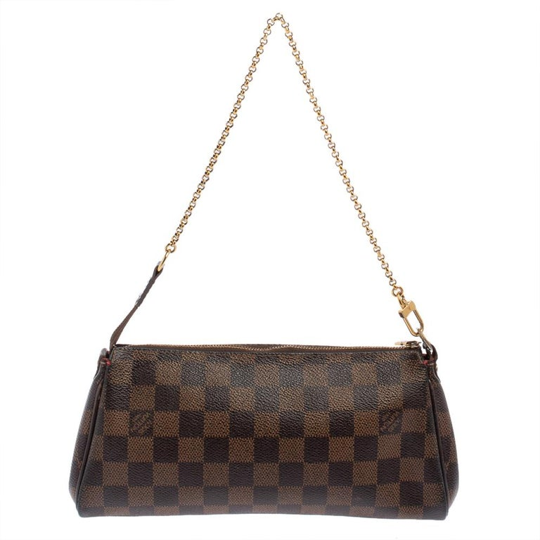 The Eva Pochette bag by Louis Vuitton showcases contemporary charm with its sophisticated shape. Made in France from Damier Ebene canvas, it features a detachable gold-tone chain handle and a top zipper. The metal plate engraved with the label's