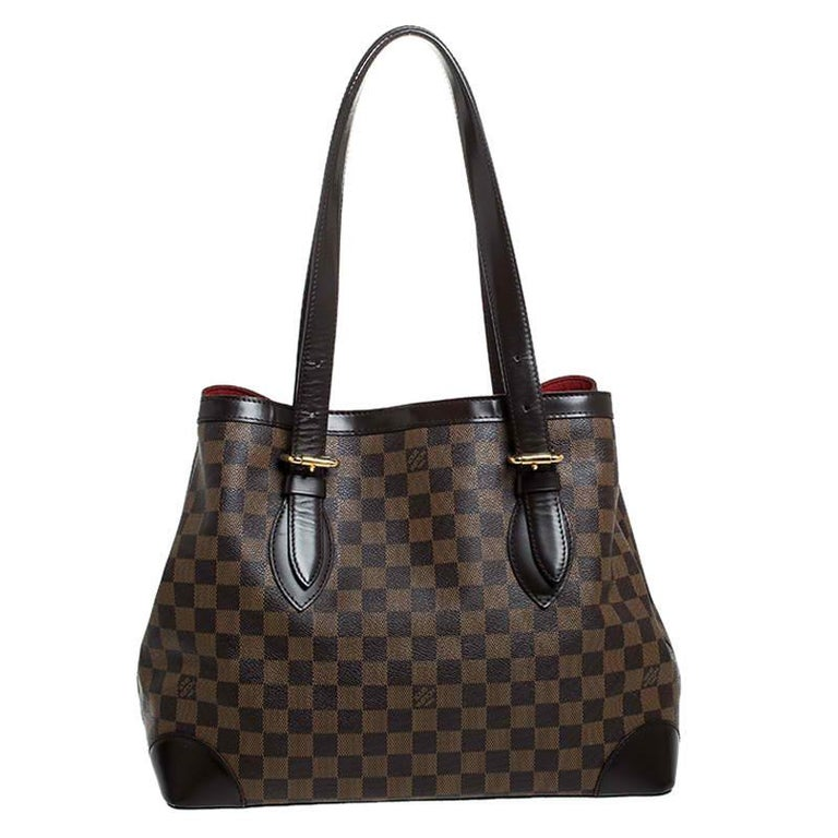 Handbags from Louis Vuitton enjoy widespread popularity owing to their high style and functionality. This Hampstead bag is no exception. Crafted from their signature Damier Ebene canvas, the bag comes with two flat top handles and a hook clasp that